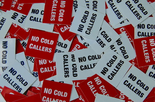 A photo of lots of red and white 'No Cold Callers' stickers.