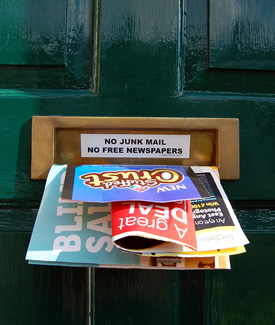 A photo showing leaflets sticking out of a letterbox with a 'No Junk Mail' sign.